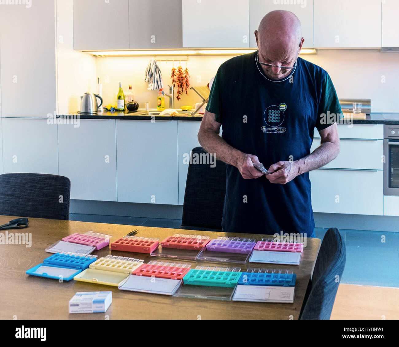 Elderly man loading pill boxes with prescribed medicines, medications,pills,10 weeks supply.Senior male sorts prescription - Stock Image