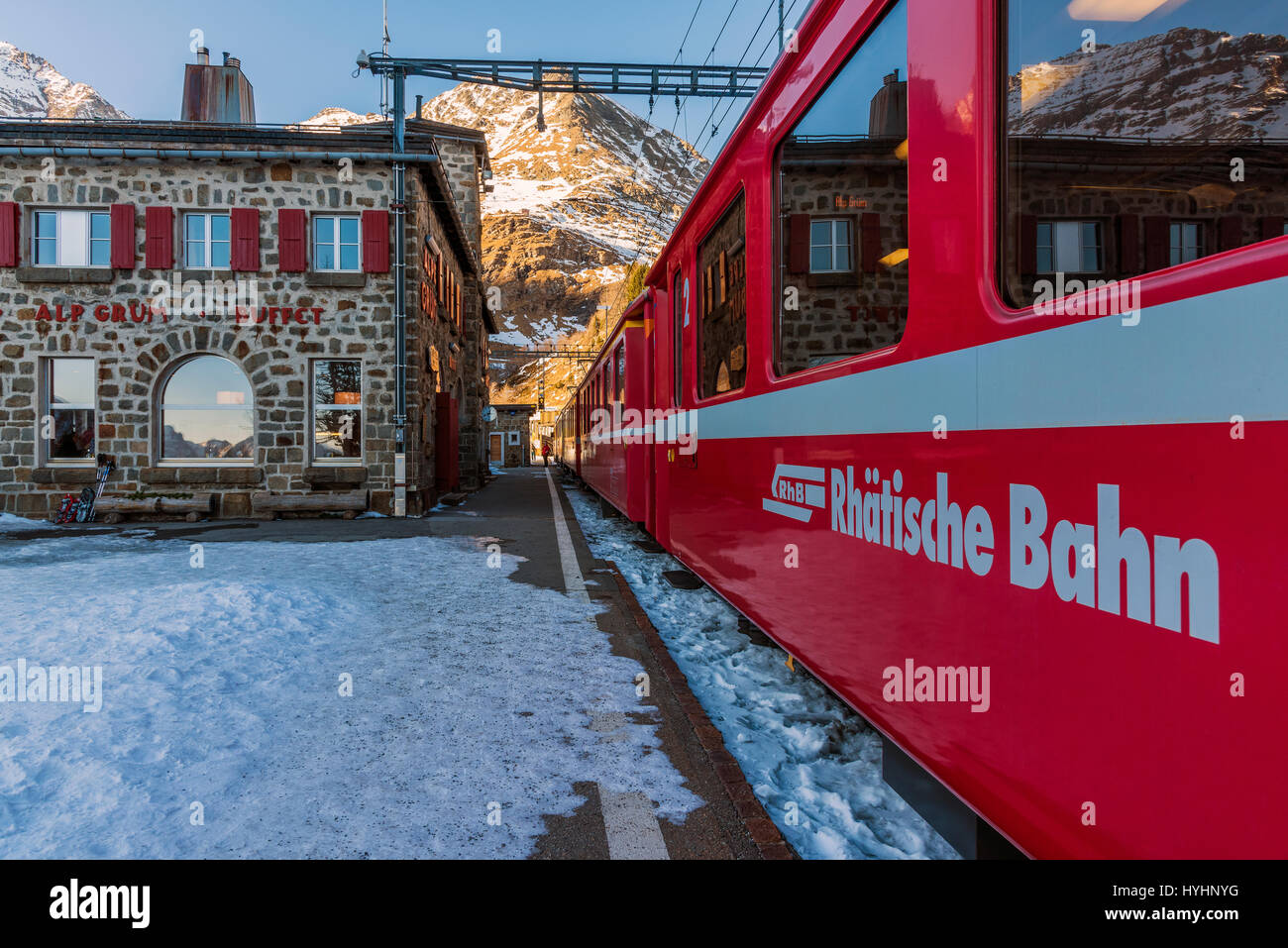 The Bernina Express red train at Alp Grum station, Graubunden, Switzerland - Stock Image