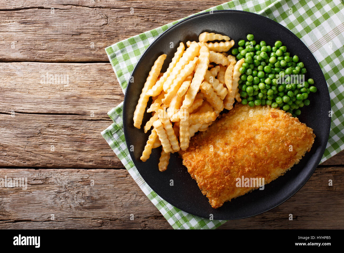 Traditional British food: Fish and chips with green peas close-up on a plate on a table. horizontal view from above Stock Photo