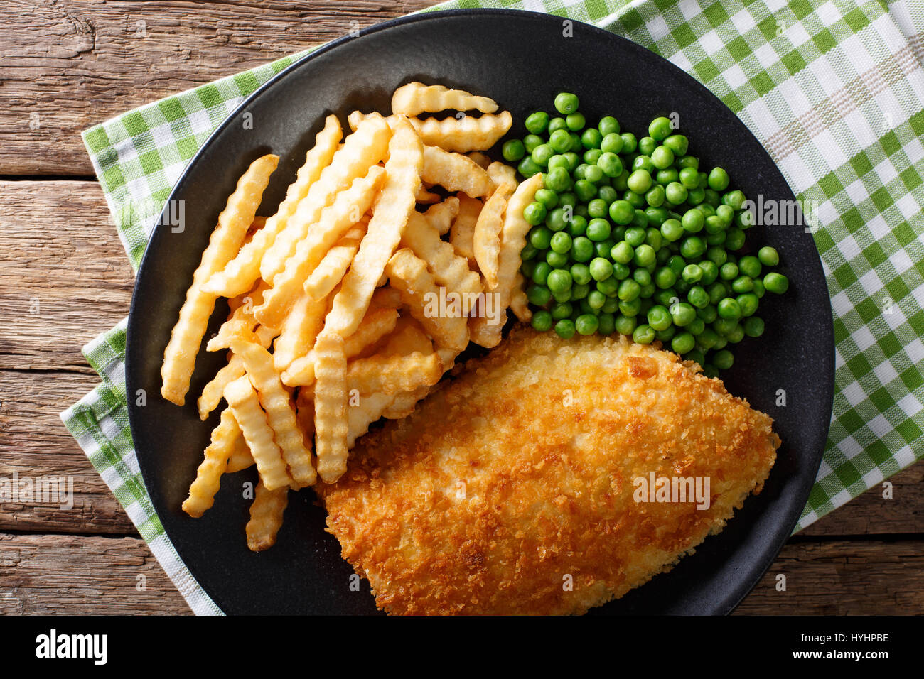 Fish and chips with green peas close-up on a plate on a table. horizontal view from above - Stock Image