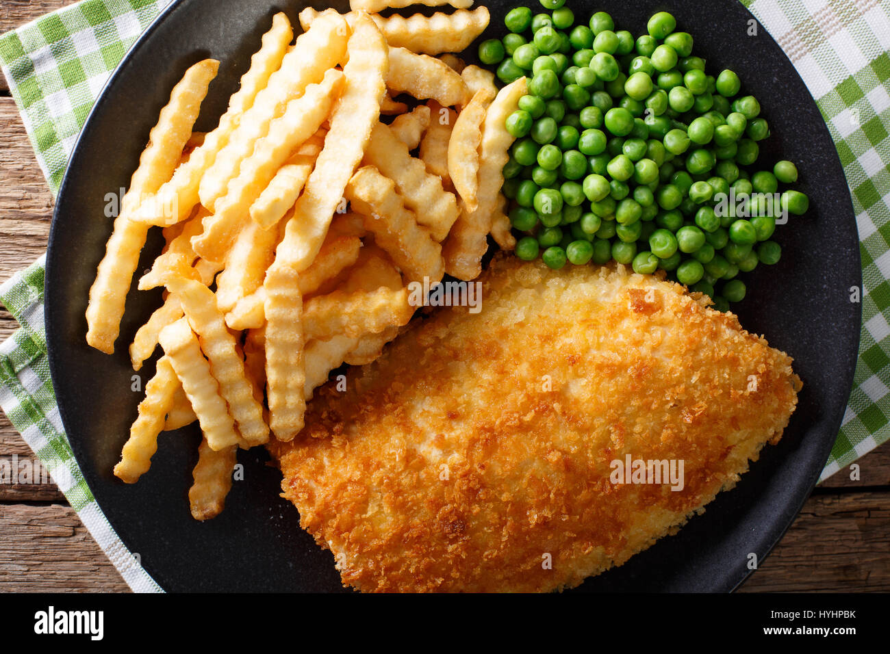 Delicious cod fish and chips with peas close-up on a plate on the table. Horizontal view from above - Stock Image