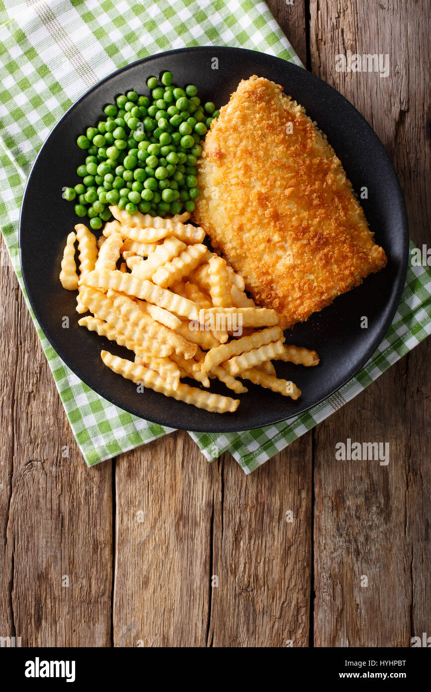Traditional British food: Fish and chips with green peas close-up on a plate on a table. Vertical view from above - Stock Image