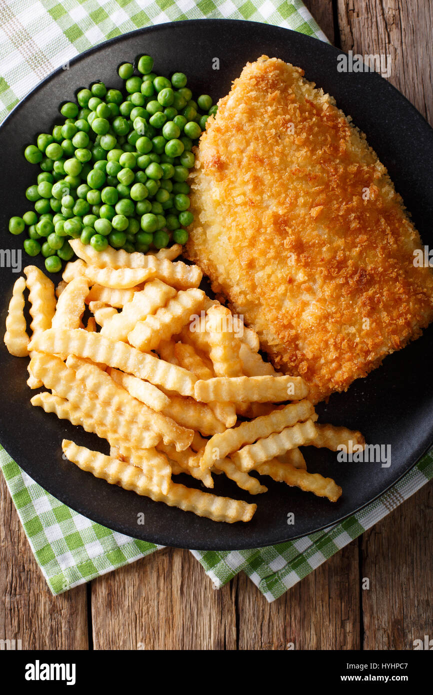 Delicious cod fish and chips with peas close-up on a plate on the table. Vertical view from above - Stock Image