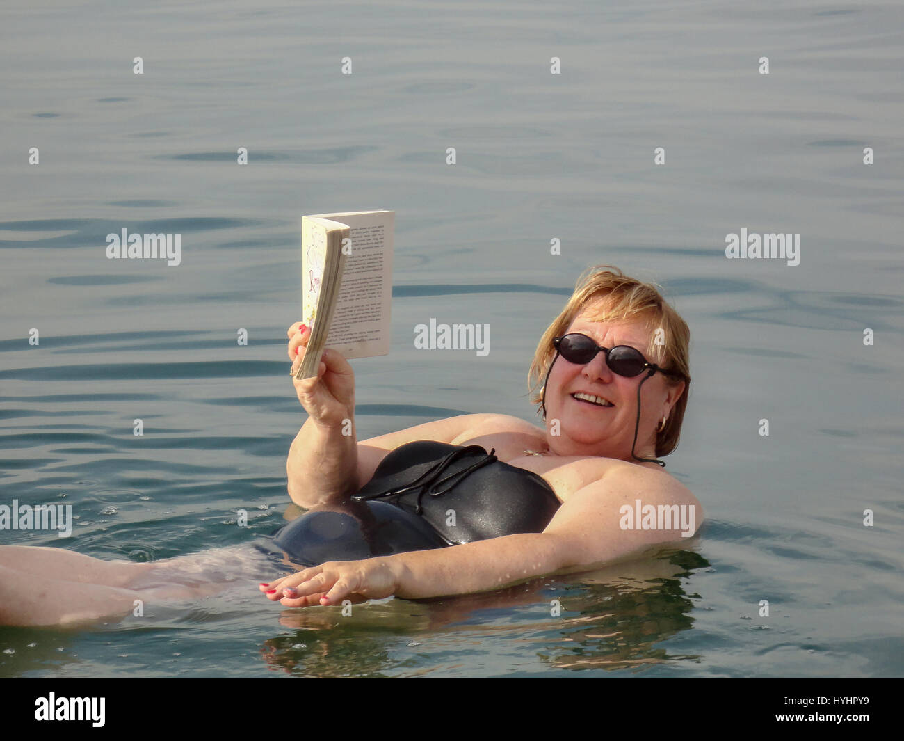 A woman floating in te Dead Sea reading a paperback book. - Stock Image