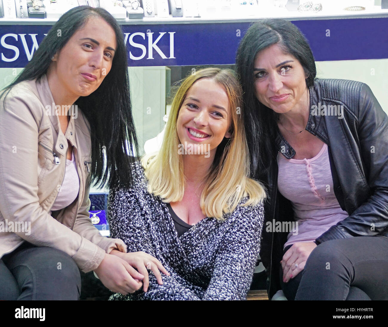Three women friends on shopping street, Peja, Kosovo. - Stock Image