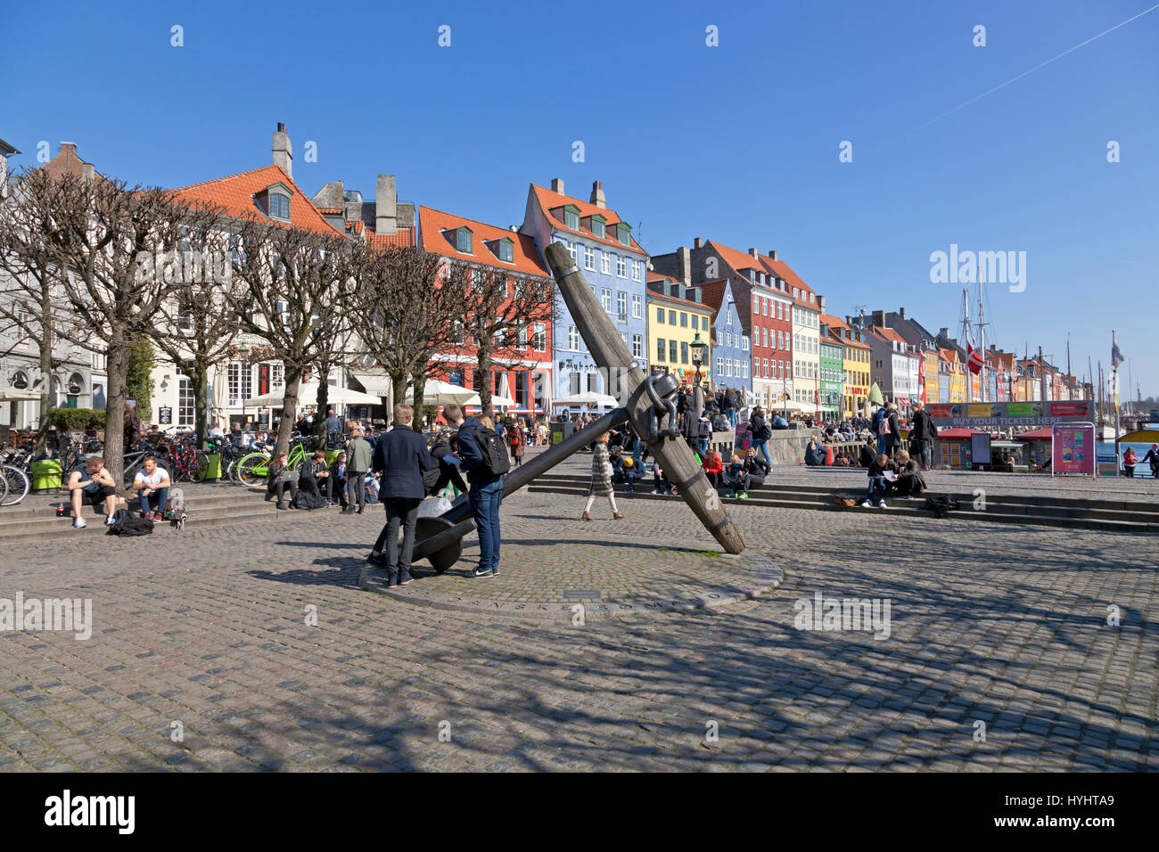 Students at the Memorial Ancher in Nyhavn, Copenhagen, on a sunny day in early April. Nyhavn is a popular urban - Stock Image