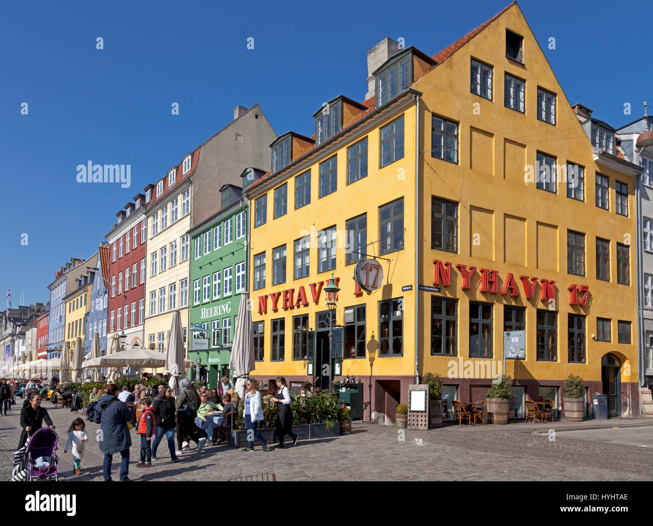 The waterfront restaurants in Nyhavn, Copenhagen, Denmark, attract many Copenhageners and tourists on a sunny spring Stock Photo