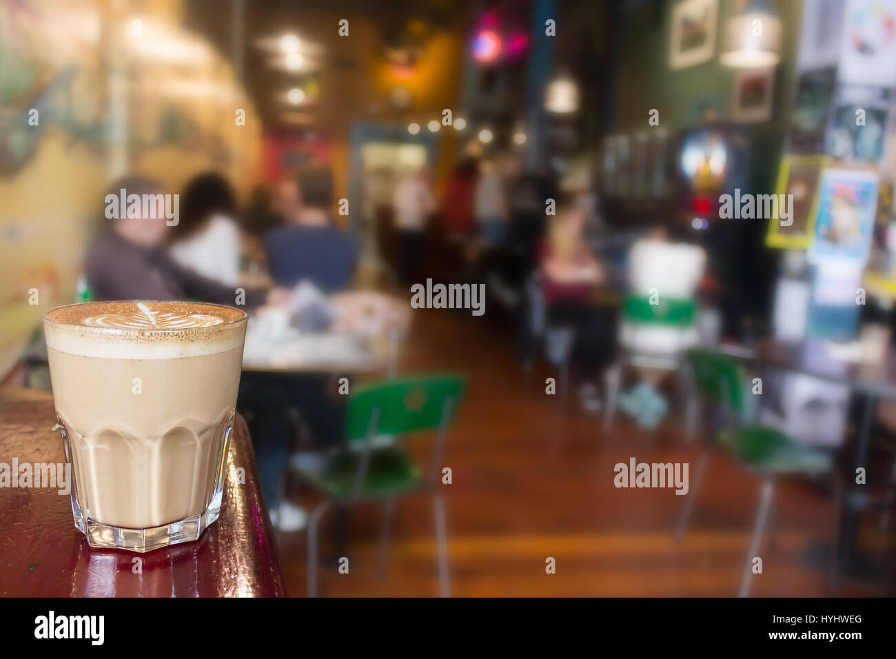 A cappuccino on on a glass closeup, interior people blurred background. - Stock Image