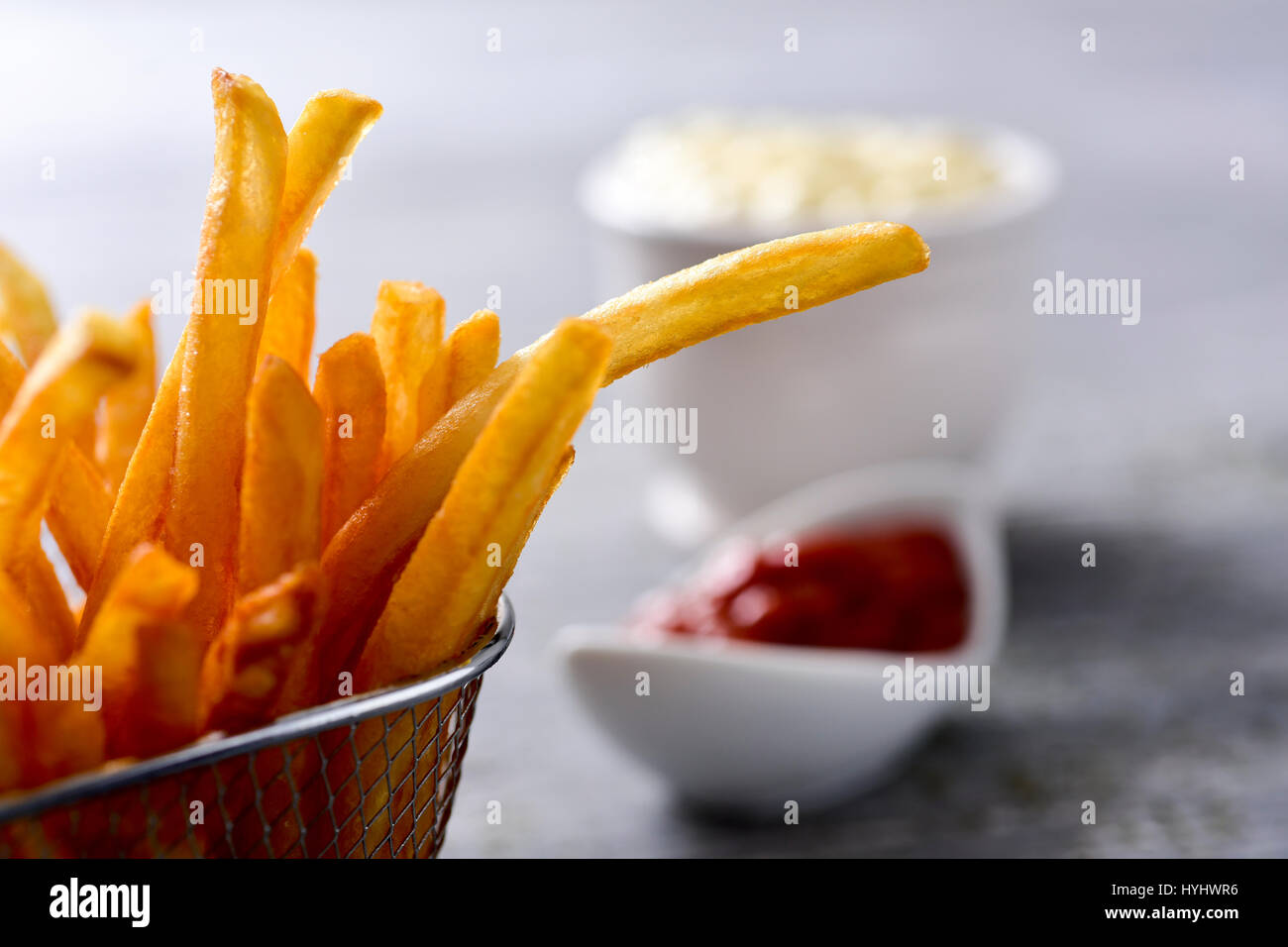 closeup of some appetizing french fries served in a metal basket and some bowls with mayonnaise and ketchup in the - Stock Image