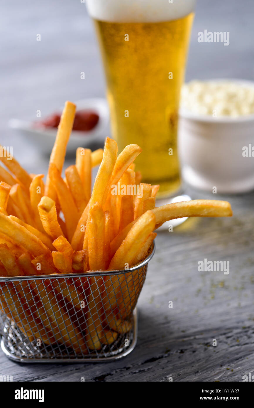 closeup of some appetizing french fries served in a metal basket on a gray rustic wooden table and a glass with - Stock Image