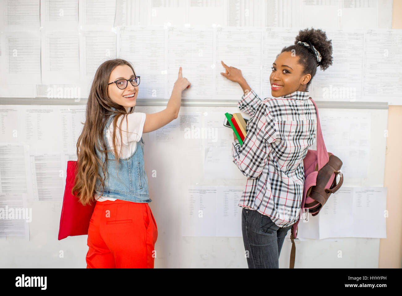 Students near the lesson schedule at the university - Stock Image