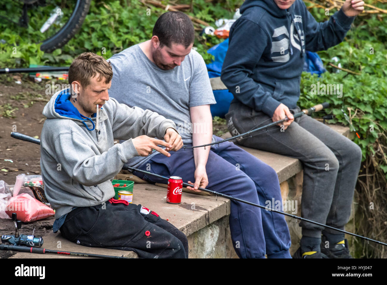 Three men fishing on a river bank whilst one smokes a joint. - Stock Image