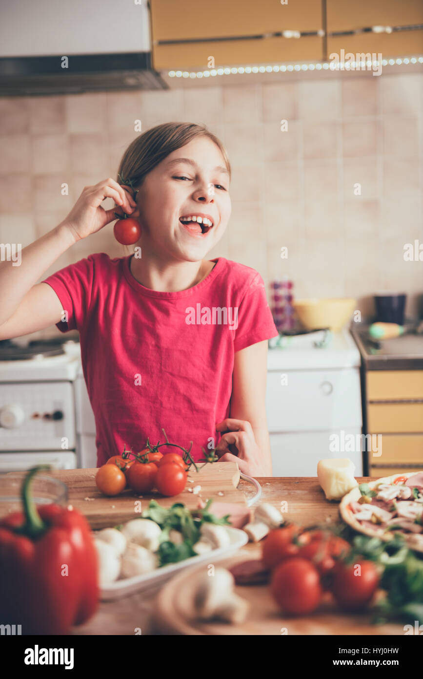 Cute little girl fooling around with tomato in the kitchen - Stock Image