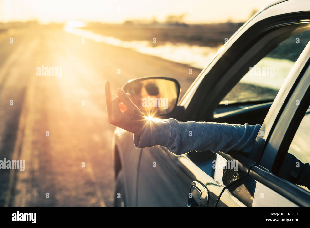 Woman driver shows midle finger on the road Stock Photo
