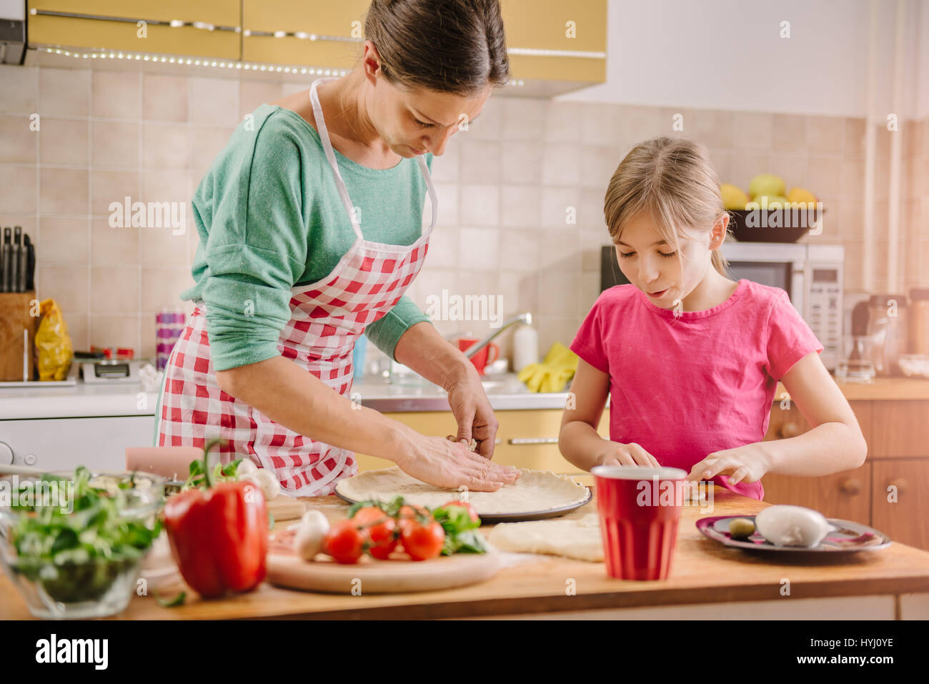 Mother and daughter preparing pizza in the kitchen - Stock Image