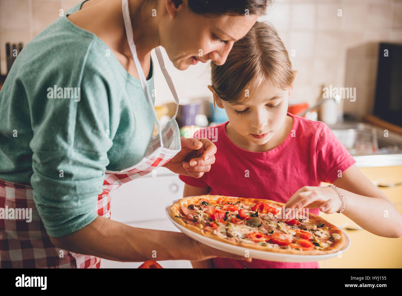 Mother and daughter tasting fresh baked pizza - Stock Image