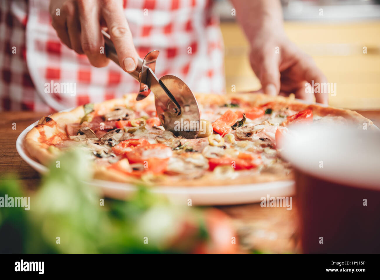 Woman cutting fresh baked pizza - Stock Image