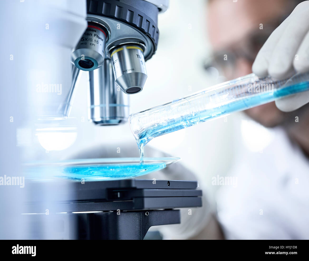 Chemist studying blue liquid under microscope, Austria - Stock Image