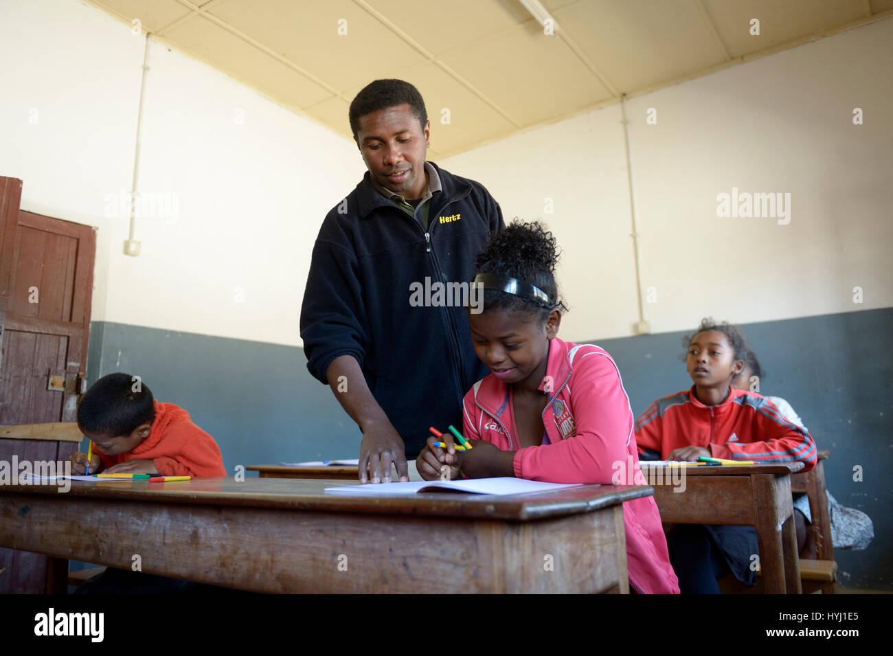 Teacher helping a female student, 15 years, Primary School, Fianarantsoa, Madagascar - Stock Image