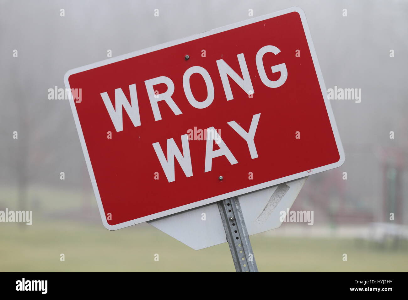 Bowed rectangular red road sign with the inscription 'wrong way' mounted on a metal support. Road sign prohibiting - Stock Image