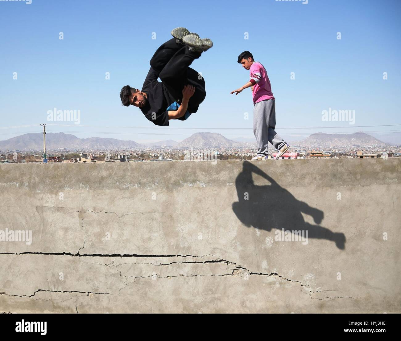 Kabul, Afghanistan. 4th April, 2017. An Afghan youth performs his Parkour skills from top of a wall in Kabul, capital - Stock Image