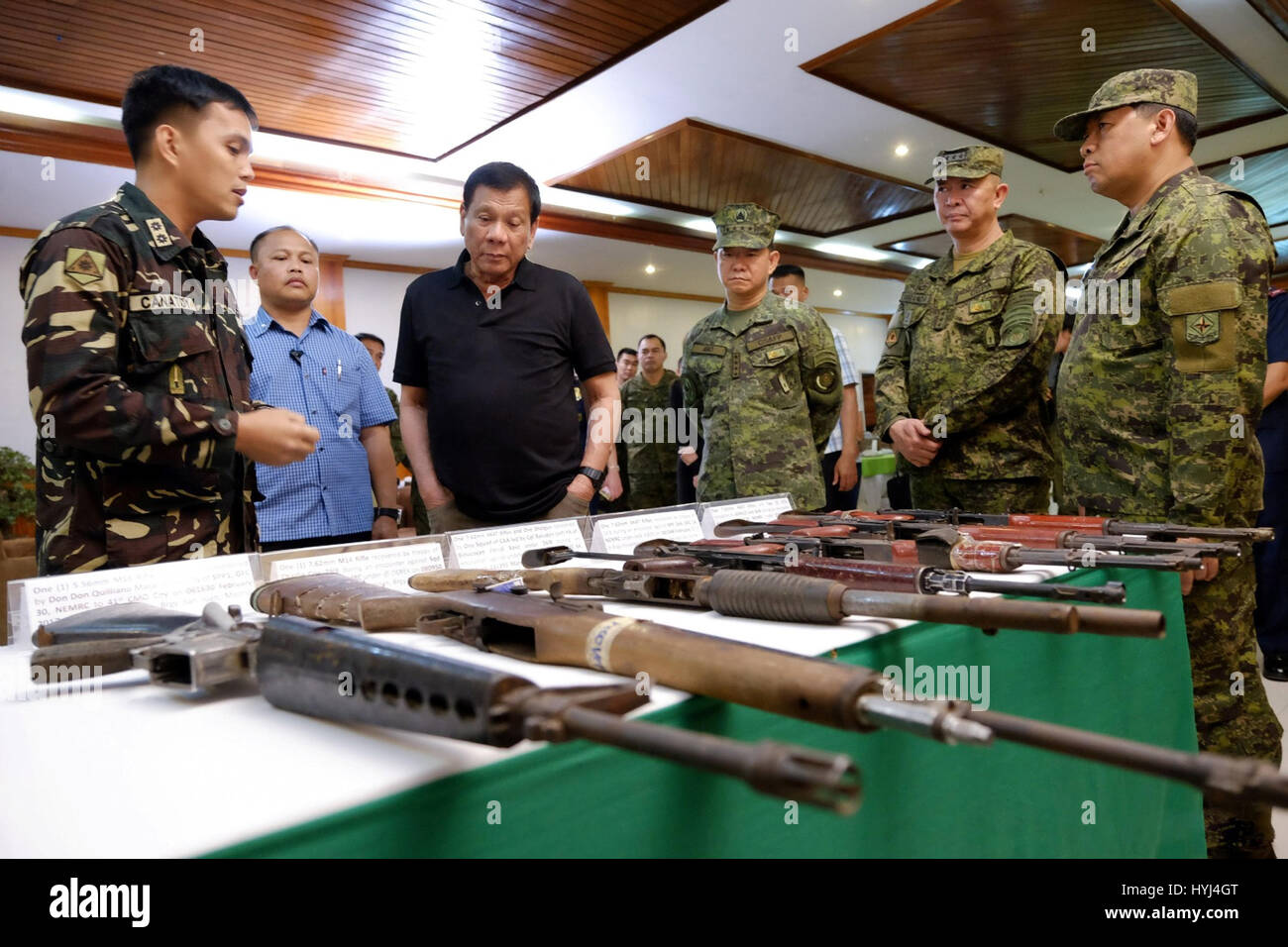 Philippine President Rodrigo Duterte examines firearms seized from the New Peoples Army during a visit to the 4th - Stock Image