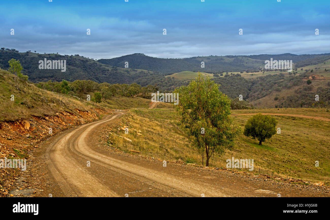 Narrow dirt road winding through vast  landscape of forested hills and valleys of Great Dividing Range under blue - Stock Image