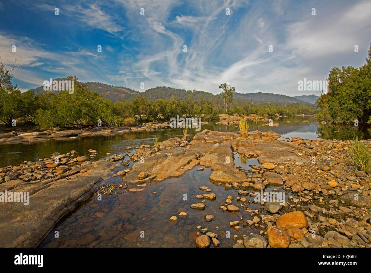 Panoramic view of rocky course of Mann River hemmed with forests & with ranges on horizon under blue sky near - Stock Image