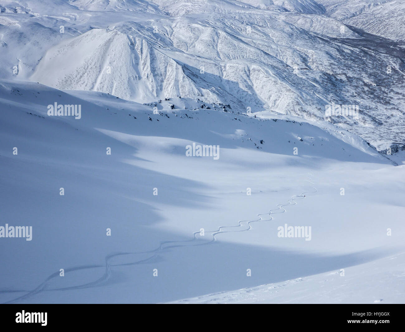 Skiers making two fresh tracks down a vast mountain valley in a snow covered landscape. - Stock Image