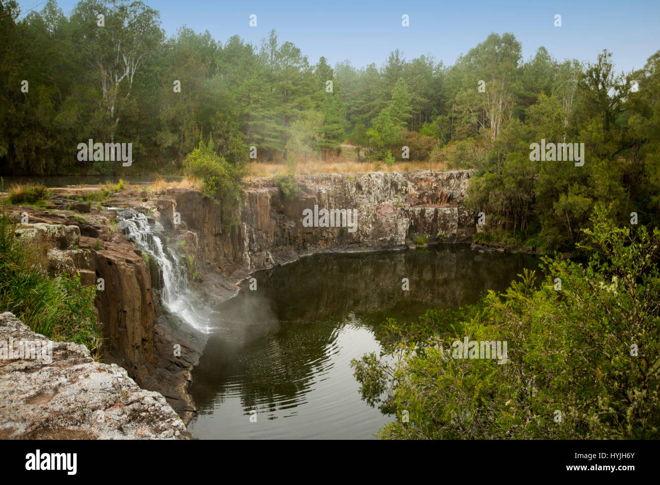 Waterfall cascading over high rocky cliff into calm waters of deep pool at Tooloom falls among forests in northern - Stock Image