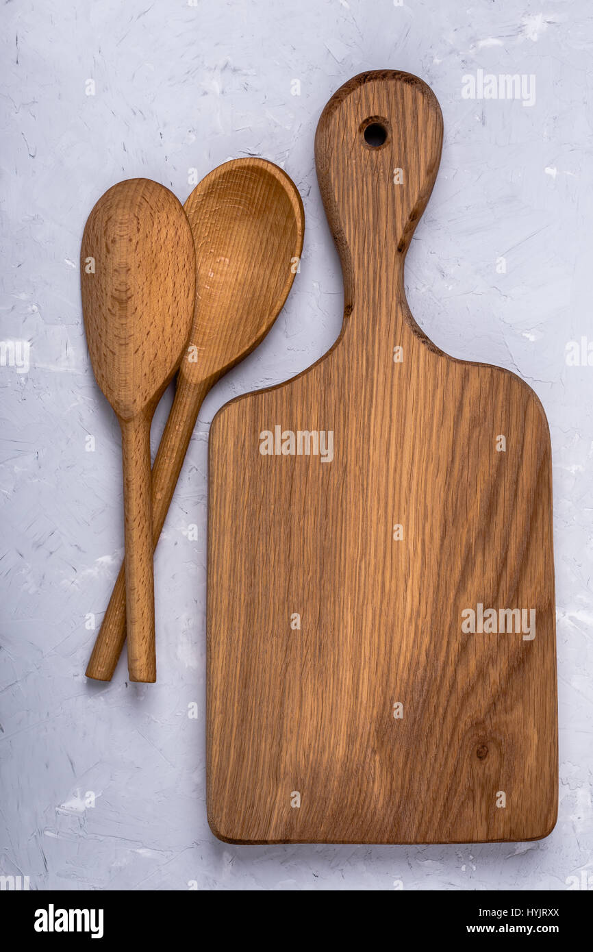 Oak wood cutting board and spoon on light gray color plaster