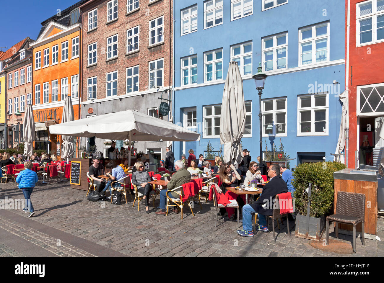 The historic waterfront restaurants in Nyhavn, Copenhagen, Denmark, attract many Copenhageners and tourists on a - Stock Image