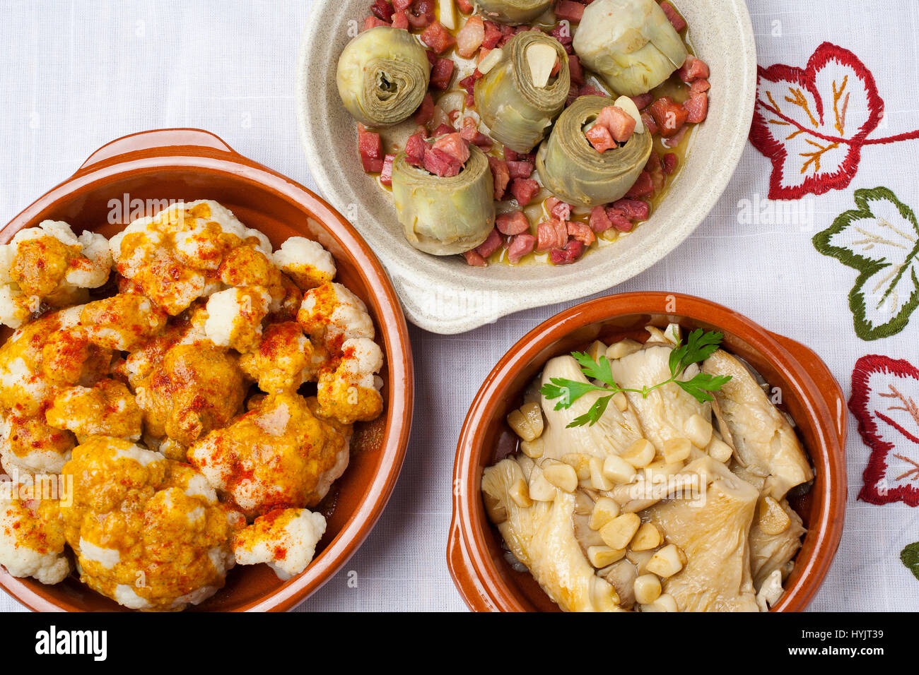 Food Tapas. Traditional gastronomic dishes of the Spanish gastronomy. Cauliflower with pimenton, artichokes with - Stock Image
