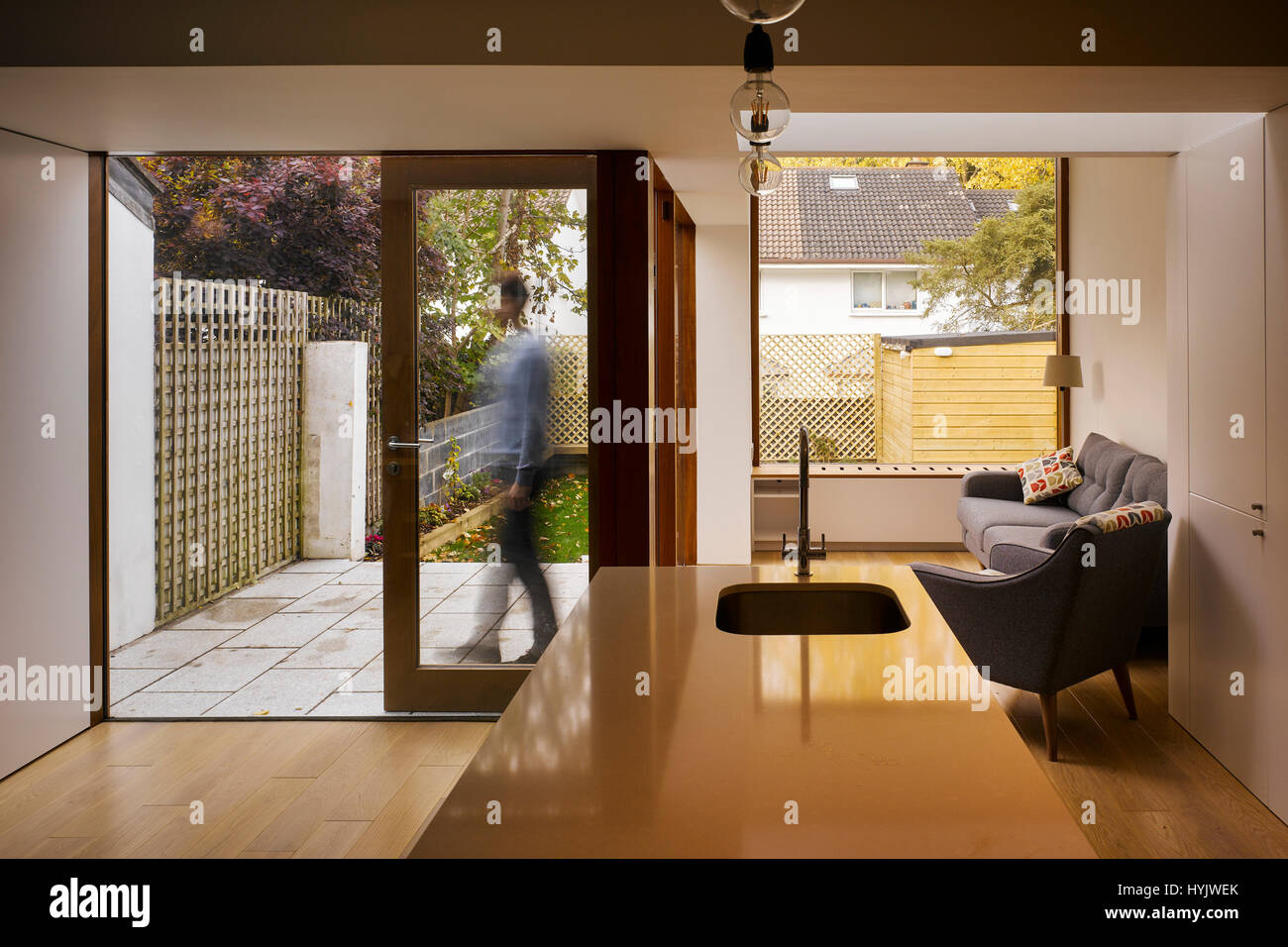 Interior view of living area showing counter, sliding door open and figure. Extension to House, Stillorgan, Dublin, - Stock Image