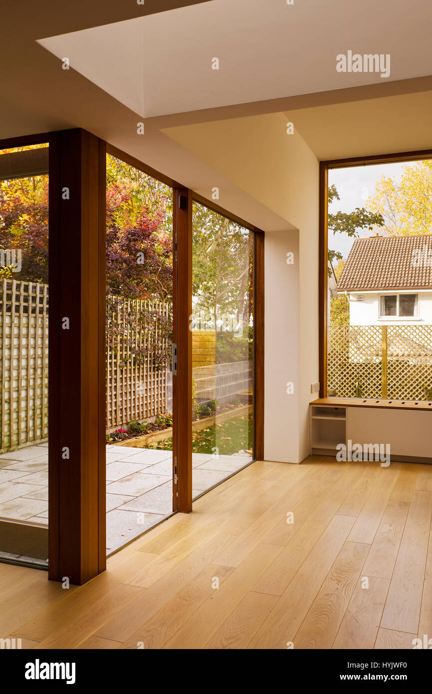 Interior view of living area showing glass doors and timber floor. Extension to House, Stillorgan, Dublin, Ireland. - Stock Image