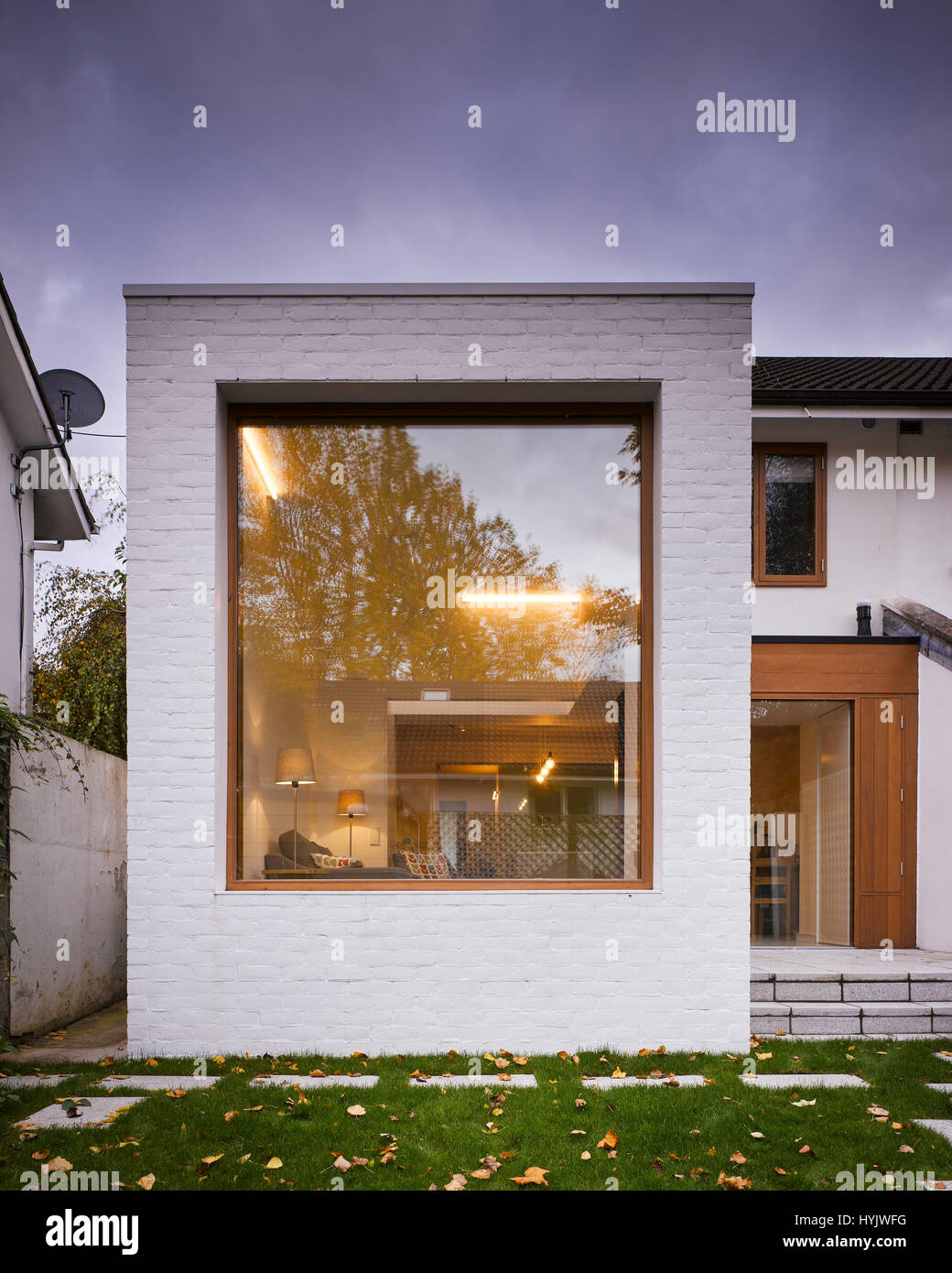 Exterior view of extension at dusk showing interior lighting. Extension to House, Stillorgan, Dublin, Ireland. Architect: - Stock Image