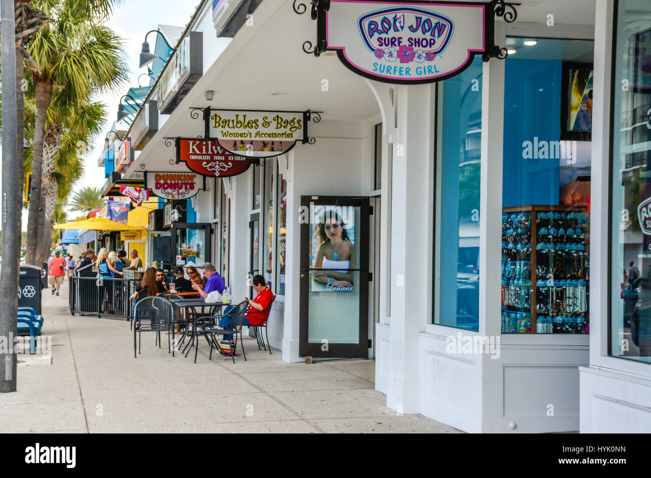 A Sidewalk View Of Retail Storefronts And Restaurants With Patio