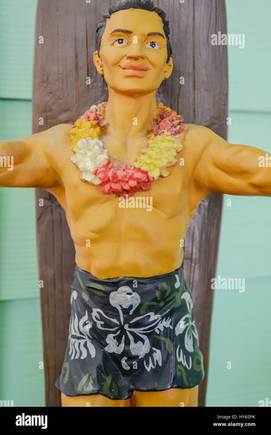 A vintage Hawaiian themed doll like sculpture, of a man with lai, tropical print swim trunks & wooden surfboard - Stock Image