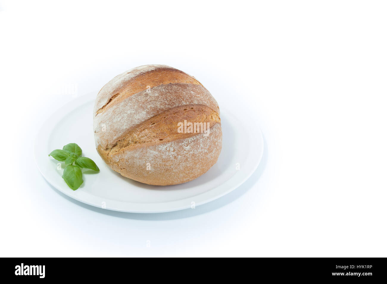 Full rustic loaf of bread with basil leaves on a white dish isolated on white background - Stock Image