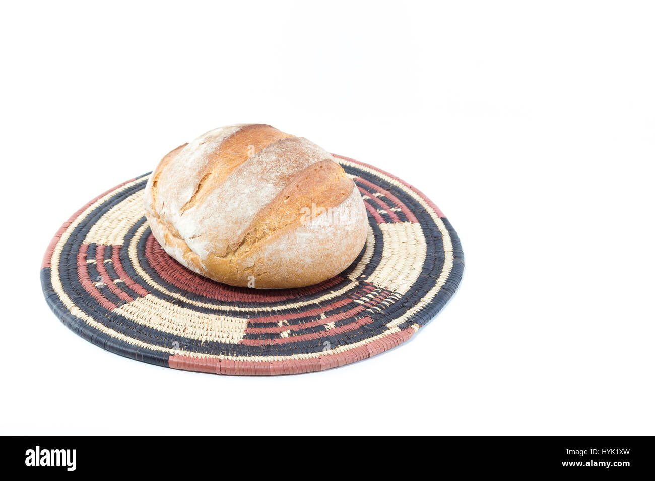Crusty loaf of bread on a bamboo straw rustic placemat isolated on white background - Stock Image