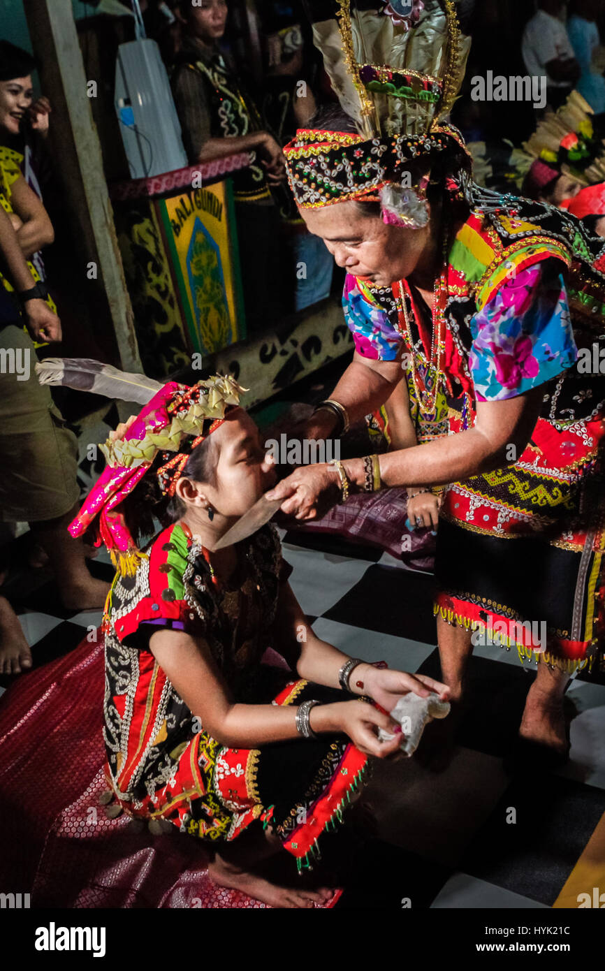 An old Dayaknese woman performs a blessing ritual to a young girl at the longhouse of Bali Gundi in Putussibau, - Stock Image