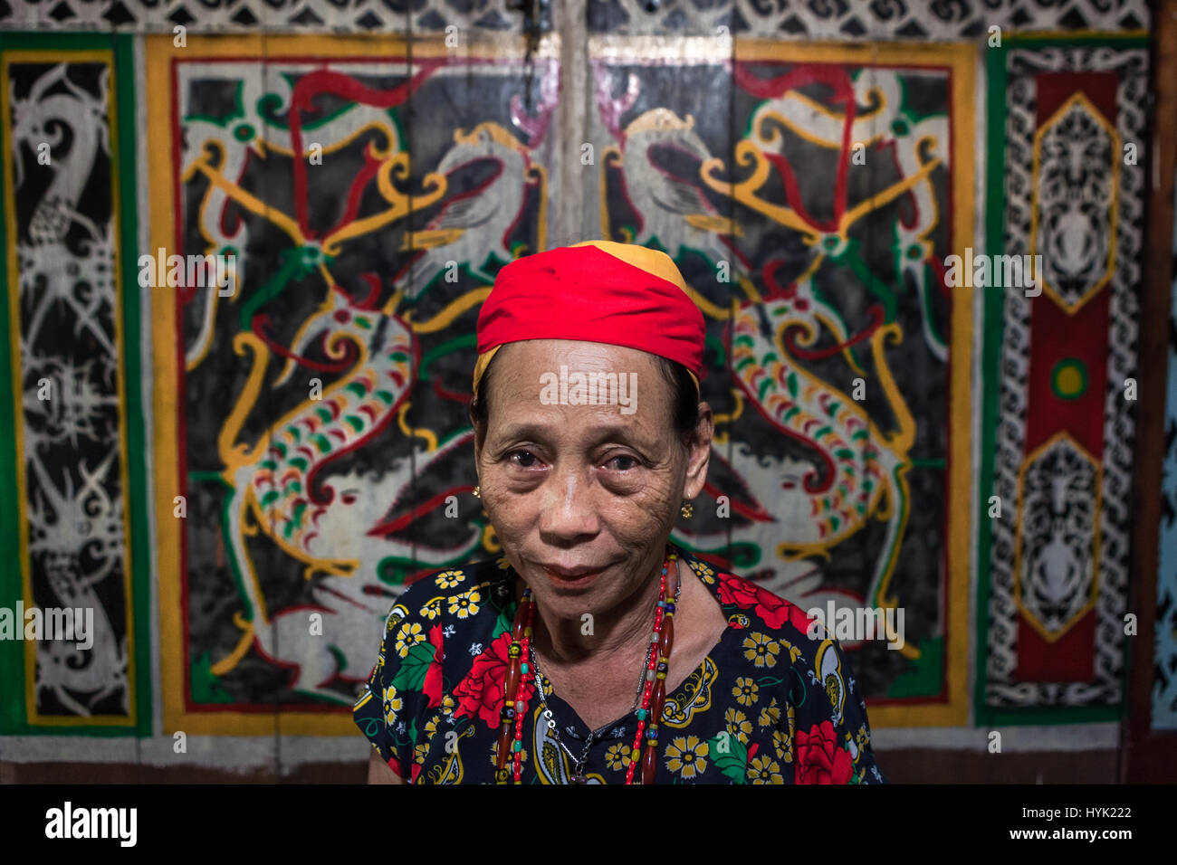 Woman in Dayak Taman traditional attire poses for a portrait with Dayaknese wall painting as the background. © - Stock Image