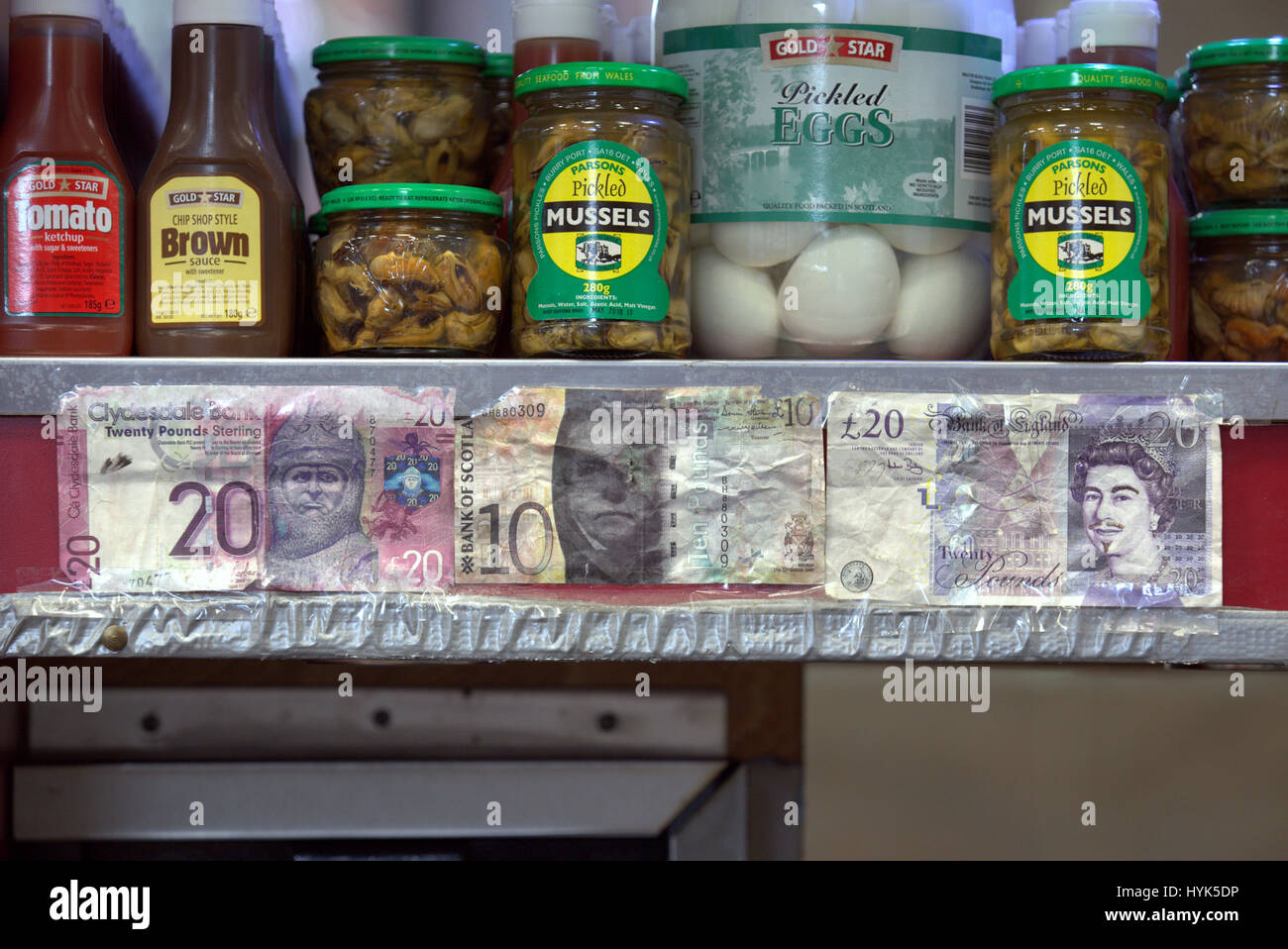 fake currency notes pinned to a till above in a fish and chips shelf  take away shop - Stock Image