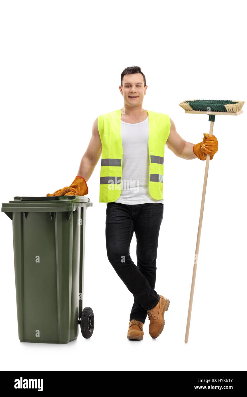 Full length portrait of a waste collector with a broom and a garbage bin isolated on white background - Stock Image