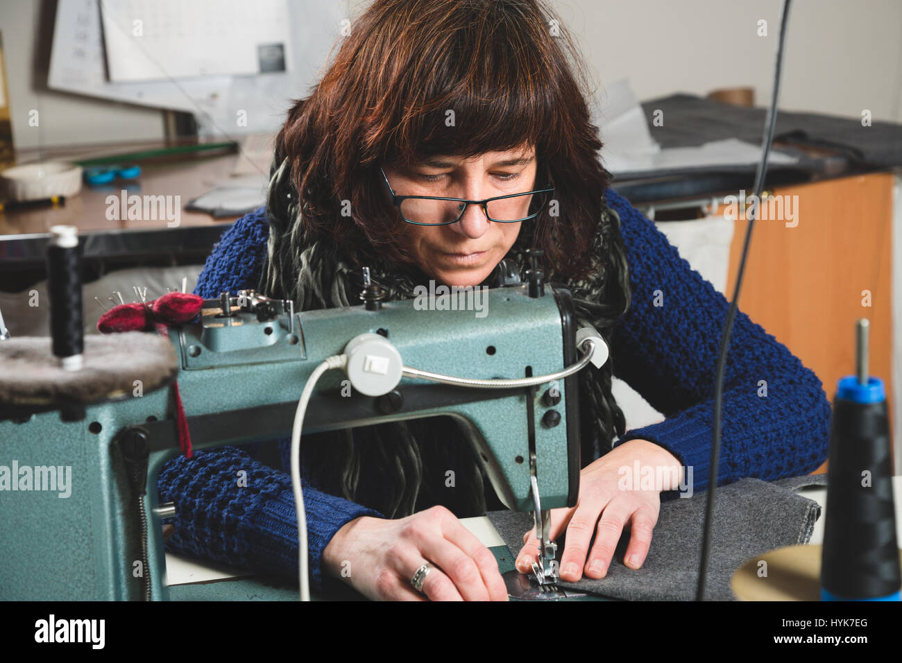 Seamstress sewing with a professional sewing machine - Stock Image