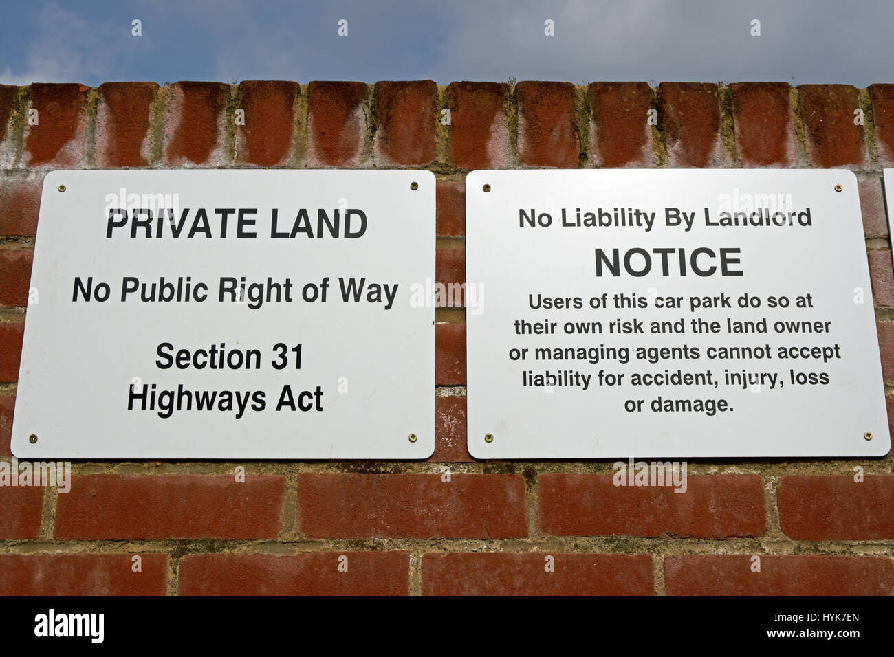 signs stating private land, no public right of way, section 31 highways act, and no liability by landlord of car - Stock Image