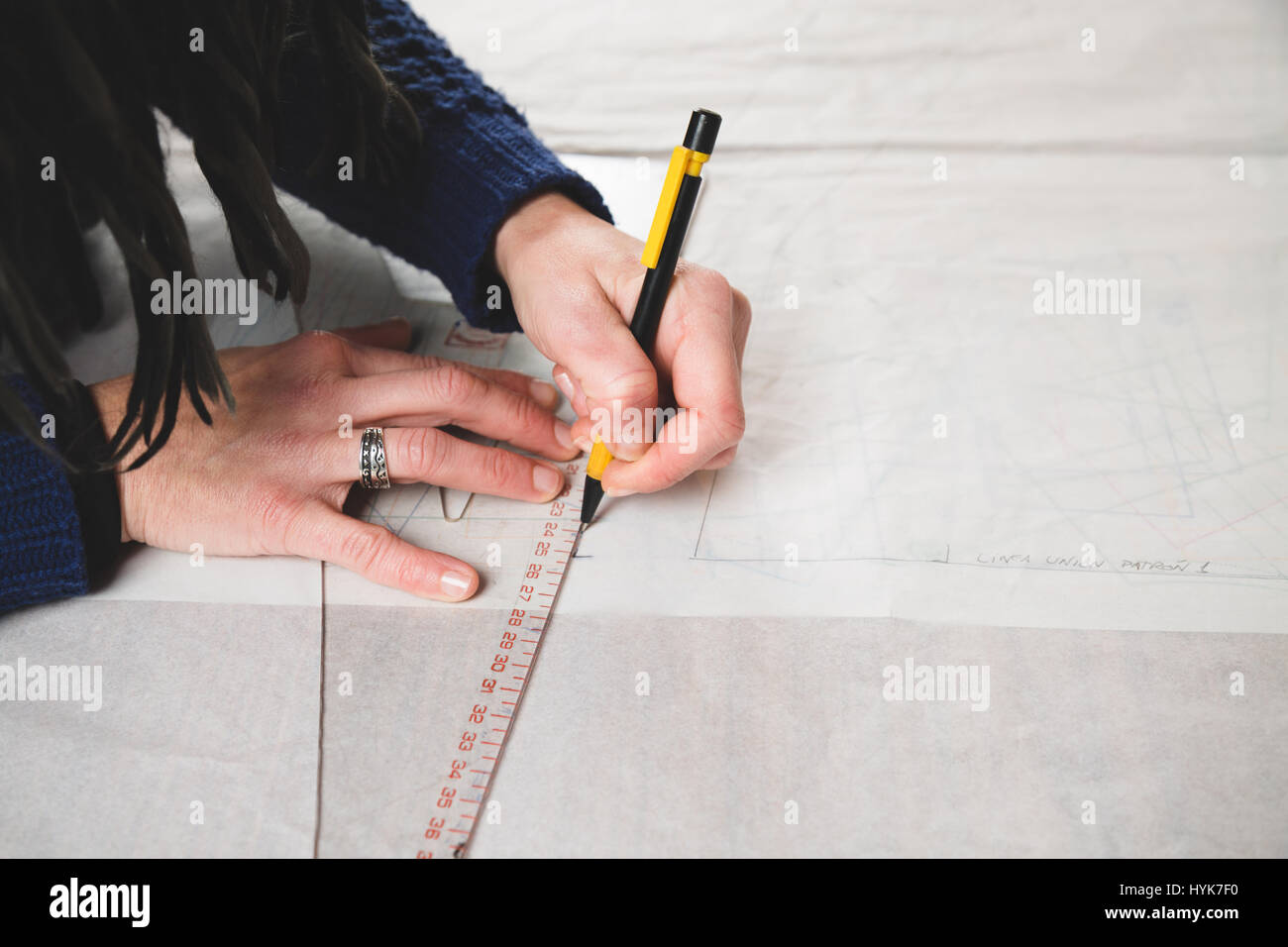 Hands of seamstress drawing templates in tracing paper using rules - Stock Image