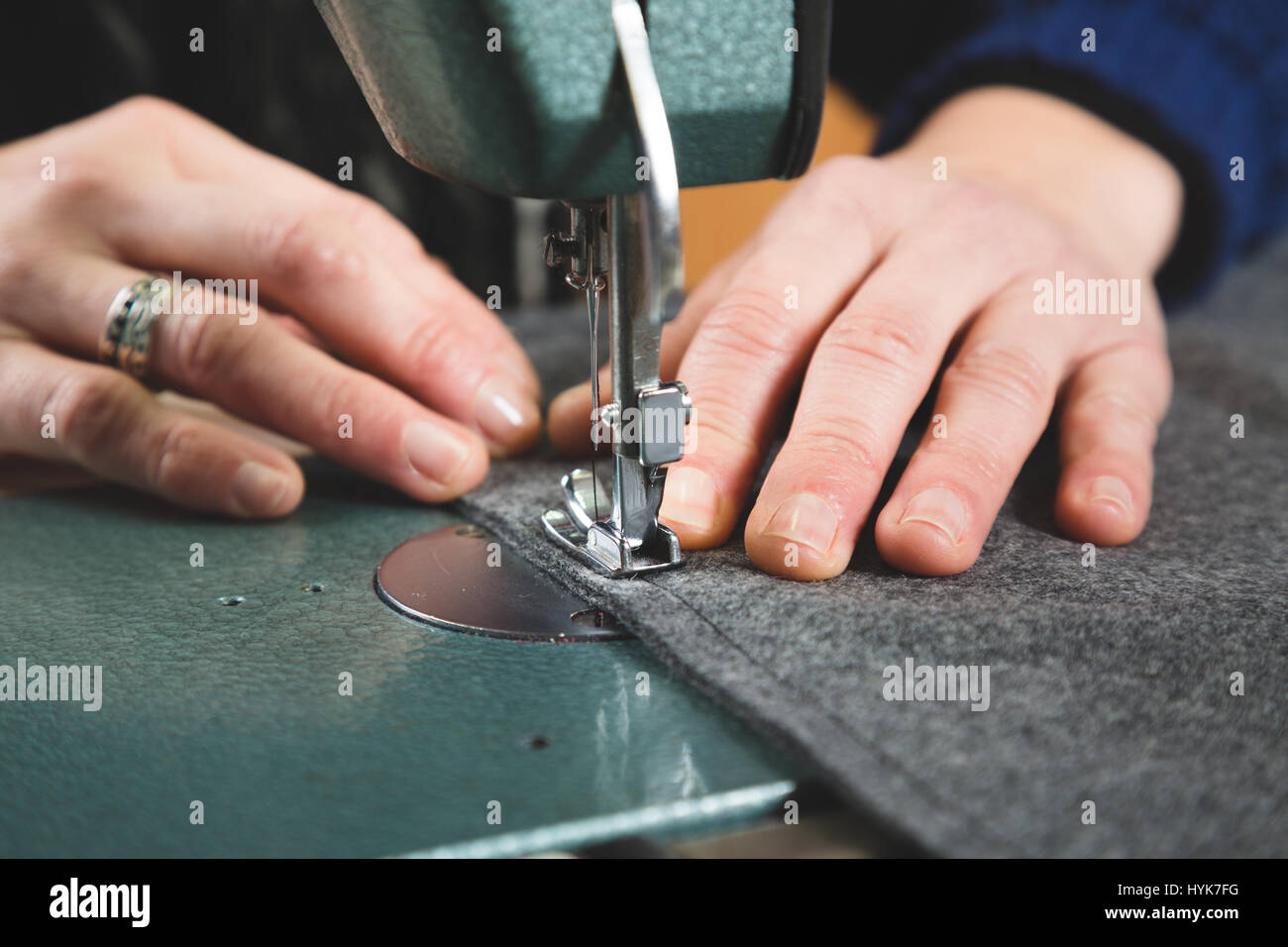 Hands of seamstress sewing with a professional machine a grey fabric - Stock Image