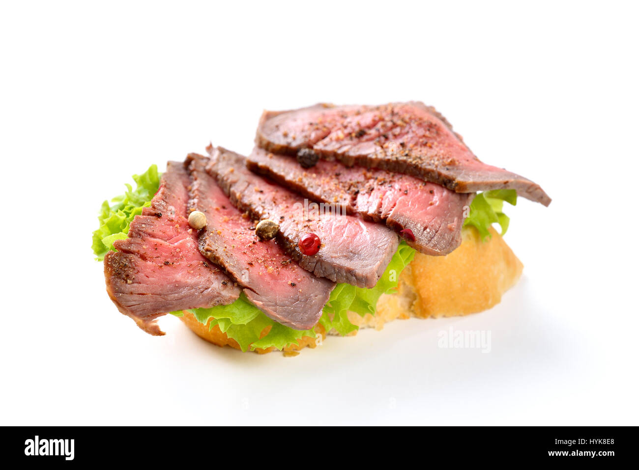 Roasted beef fillet with pepper on a slice of baguette with a leaf of salad - Stock Image