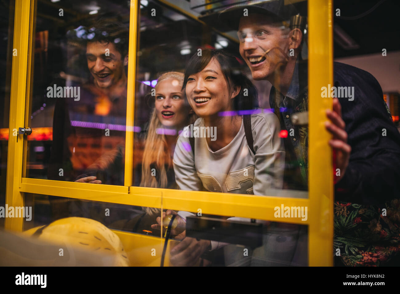Happy young friends playing toy grabbing game at amusement park. - Stock Image
